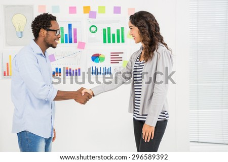 Young smiling business people shaking hands in the office - stock photo