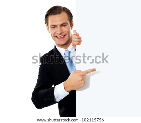 Young smiling business person pointing towards blank signboard - stock photo