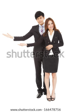 Young smiling business woman and man with welcome gesture - stock photo