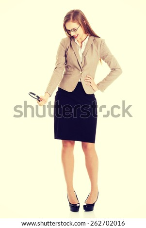 Young smiling business woman looking into a magnifying glass. - stock photo
