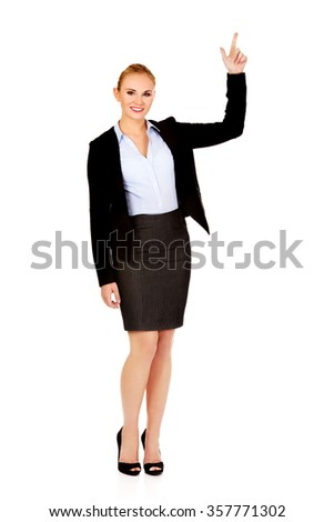 Young smiling business woman pointing up. - stock photo