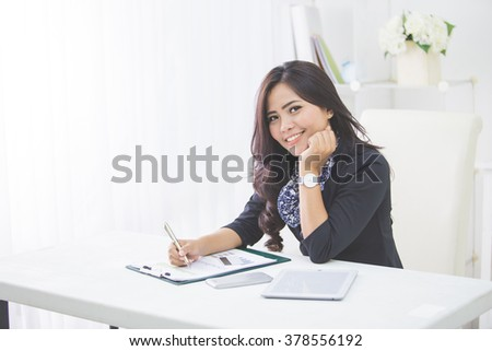 Young smiling business woman working on her paperwork in her office