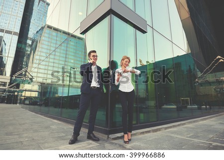 Young smiling businessman is talking on mobile phone, while his secretary with cell telephone is hand is checking time. Two successful entrepreneur is using cellphones during their work break - stock photo
