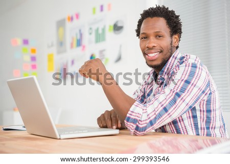 Young smiling businessman looking at the camera in the office