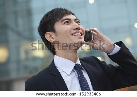 Young smiling businessman on the phone looking up - stock photo