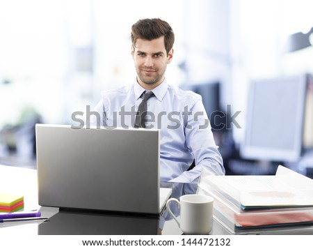 Young smiling businessman sitting in office with laptop on desk - stock photo