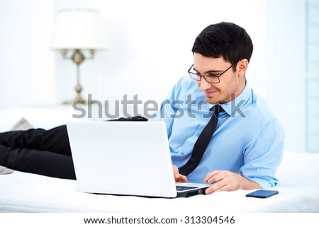 Young smiling businessman using laptop while lying on big white bed in cozy hotel room