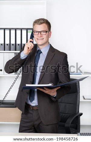 Young smiling businessman with glasses is phoning while standing at the desk in the office. In one hand he is holding a file. A shelf is in the background. The man is looking to the camera.