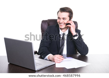 Young smiling businessman working at the office on laptop, talking on cell phone and smiling.