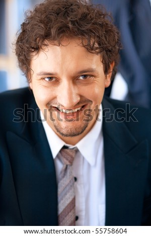 Young smiling businessman working on laptop in the office