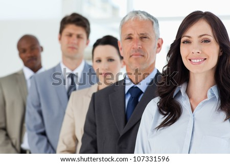 Young smiling businesswoman followed by her full team - stock photo
