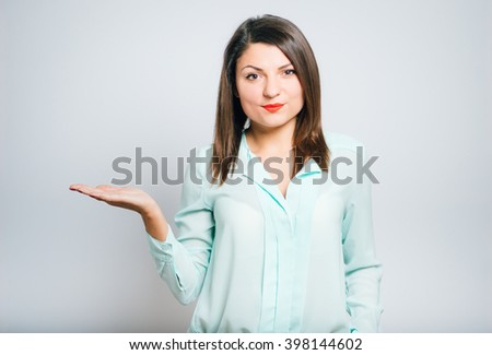 Young smiling businesswoman holding out her hand as if she were displaying something.You can add any text or object on the palm of her hand. - stock photo