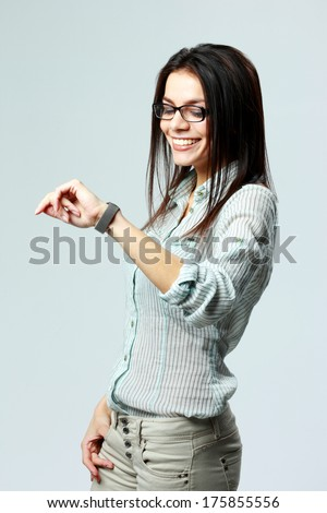 Young smiling businesswoman looking at her watch on wrist on gray background - stock photo