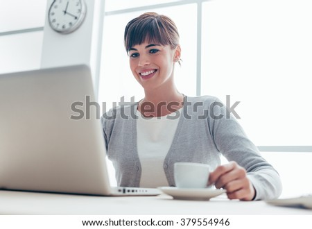 Young smiling businesswoman sitting at office desk, working with a laptop, connecting to internet and having a coffee break