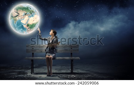 Young smiling businesswoman sitting on bench with book in hands. Elements of this image are furnished by NASA - stock photo