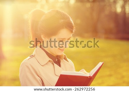 Young smiling businesswoman,student professional outdoors  holding a red ,journal writing in it.Businesswoman smiling,Life style, - stock photo