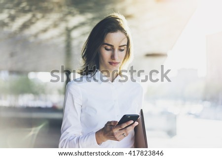 Young smiling businesswoman using modern smartphone outdoors, professional female lawyer searching information in internet via mobile phone near her office, flare light - stock photo