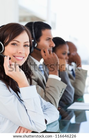 Young smiling call centre agent looking at the camera while working hard - stock photo