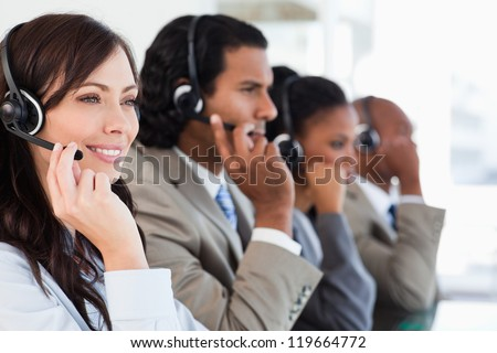 Young smiling call centre employee working hard and accompanied by her team - stock photo