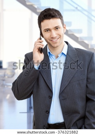 Young smiling caucasian businessman with mobile phone in hand at business office. Suit no tie, standing, looking at camera. - stock photo