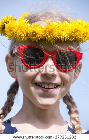 young smiling caucasian girl portrait in yellow dandelions garland on the head with two pigtail braids and red sunglasses - stock photo