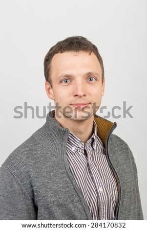Young smiling Caucasian man in casual clothing, studio portrait over white background - stock photo
