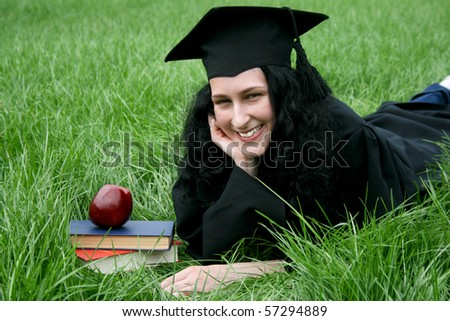 Young smiling Caucasian student laying on the grass