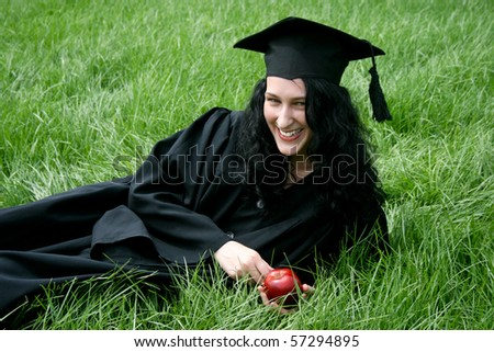 Young smiling Caucasian student laying on the grass - stock photo