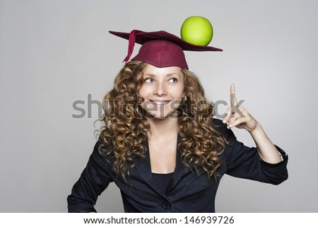 Young smiling caucasian student with an apple on her head