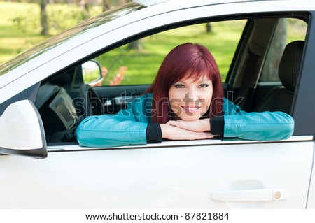 Young smiling caucasian woman in her new car outdoors - stock photo