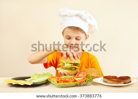 Young smiling chef shows how to cook a hamburger - stock photo