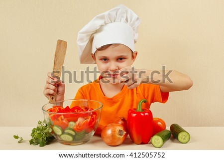 Young smiling chef shows how to cook a vegetable salad - stock photo