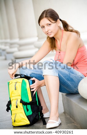 Young smiling college girl opening backpack