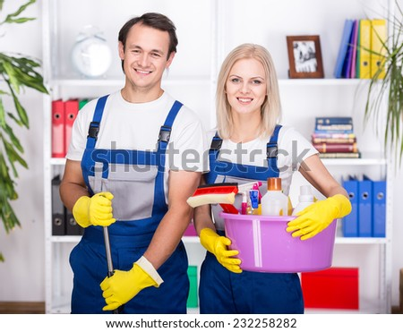 Young smiling couple are holding cleaning tools. - stock photo