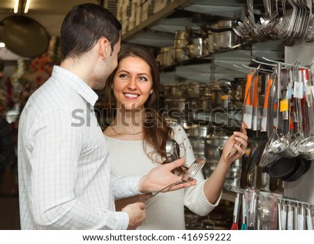 Young smiling couple chooses cooking utensils at shop