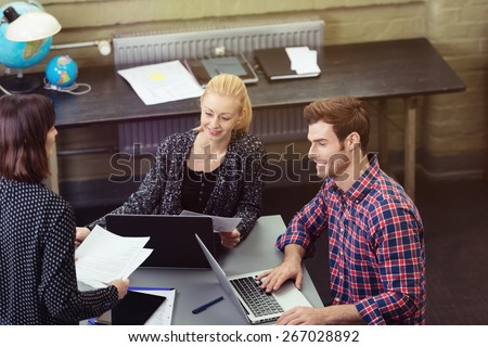Young Smiling Couple Discussing Business Project at the Table with Laptop Computers Together with a Woman. - stock photo