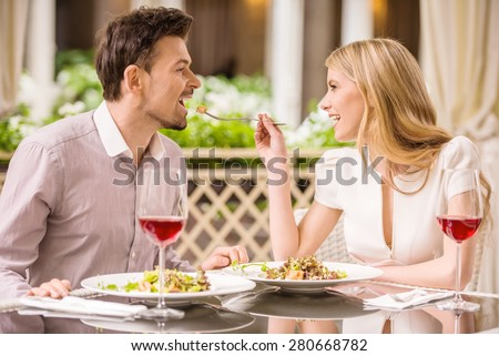 Young smiling couple enjoying the meal in gorgeous restaurant and drinking wine. Woman feeding man. - stock photo