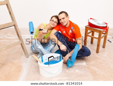 Young smiling couple having a break during home renovation