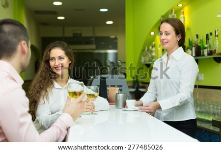 Young smiling couple having a date with wine at bar. Focus on girl - stock photo