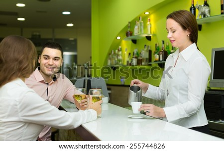 Young smiling couple having a date with wine at bar. Focus on man - stock photo