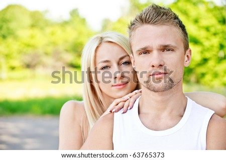 Young smiling couple in white clothes against summer park. Girl has put hands ? shoulder of guy and has leaned against them chin.