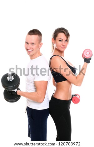 Young smiling couple lifting dumbbells in studio over a white background - stock photo