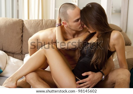 Young smiling couple looking at each other while lying in bed - stock photo