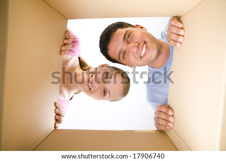 Young smiling couple looking into cardboard box. They're looking at camera. Low angle view. - stock photo