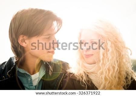 Young smiling couple looking on each other  - outdoor lifestyle portrait - stock photo