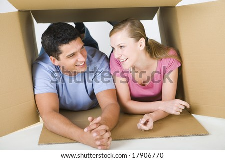 Young smiling couple lying in cardboard box and talking. Front view.