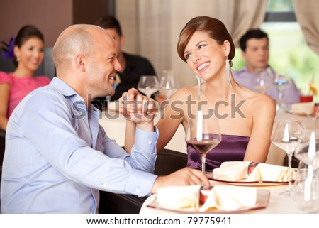 young smiling couple romancing at a restaurant table