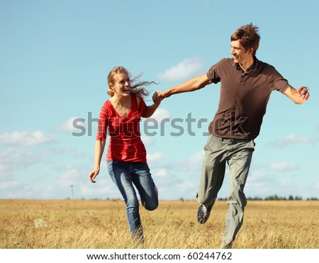 Young smiling couple running on meadow holding each other hands - stock photo
