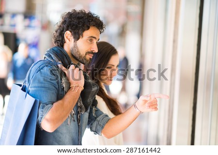 Young smiling couple shopping in an urban street. Shallow depth of field, focus on the man - stock photo
