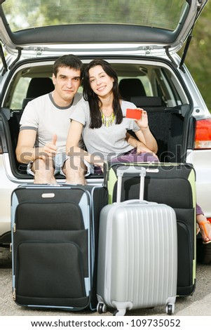 Young smiling couple sitting in the opened car bloom with travel suitcases holding empty credit card